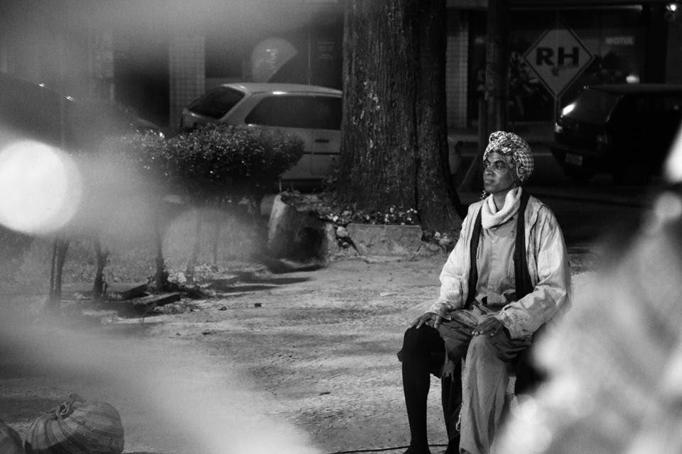 #4ParedeParaTodos #PraTodoMundoVer - Imagem em preto e branco de uma mulher negra sentada em uma cadeira em uma praça. Ao fundo, carros, árvores e plantas de diversos tamanhos.