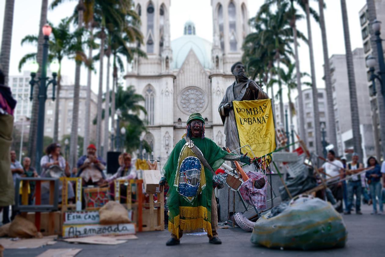 #4ParedeParaTodos #PraTodoMundoVer - Imagem colorida de um homem vestido com um figurino que remete às cores da bandeira brasileira está em um centro de uma praça. Ao redor dele, estátuas, igrejas, prédios e pessoas assistem à intervenção.