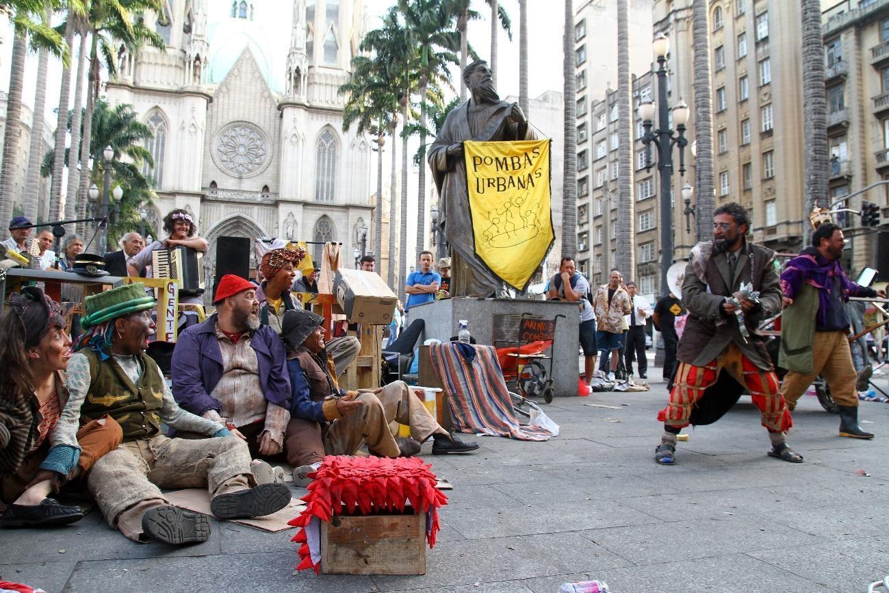 #4ParedeParaTodos #PraTodoMundoVer - Imagem colorida de um grupo de atores e atrizes em uma praça. Do lado esquerdo, um grupo deles está sentado e observam outro deles, que está em pé. Ao centro, um estandarte amarelo com o nome do grupo, Pombas Urbanas, está apoiado em uma estátua.