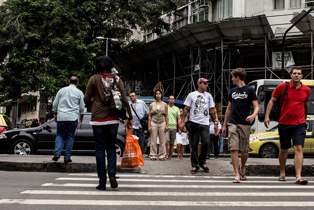 #4ParedeParaTodos #PraTodoMundoVer - Imagem colorida de uma faixa de pedestres. Nela, passam várias pessoas de idades e sexos distintos, usando roupas diferentes. Ao centro, em uma calçada, uma mulher usando roupas em cor cáqui e orelhas compridas (semelhantes à de um coelho), se posiciona em pé no meio da rua, sendo observada pelos passantes.