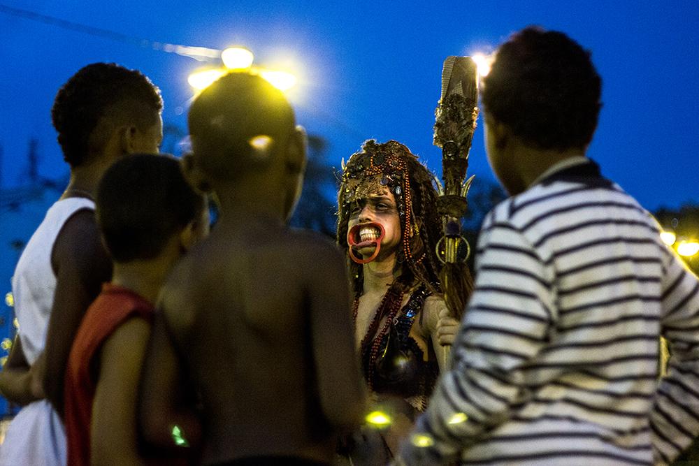 #4ParedeParaTodos #PraTodoMundoVer - Imagem colorida de crianças e adolescentes, em sua maioria negros, com roupas distintas, observando uma mulher vestida com adereços brilhantes no rosto e segurando um cetro. Ao fundo, as luzes do poste iluminam o ambiente.