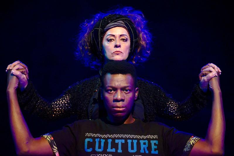 #4ParedeParaTodos #PraTodoMundoVer - Imagem colorida de um ator negro e uma atriz branca olhando para nós. O homem está de costas para a mulher e um pouco abaixo dela e ambos estão com os dedos entrelaçados.