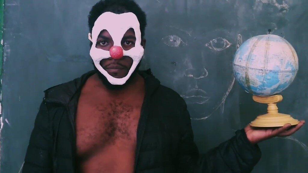 Imagem colorida de um homem negro diante de um quadro escolar. Ele veste camisa social preta aberta e usa uma máscara branca com nariz vermelho. Com sua mão direita, ele segura um globo terrestre.