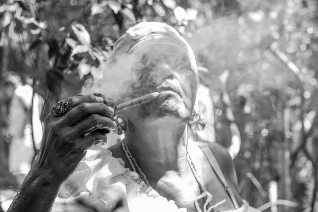 Imagem em preto e branco. Rosto de uma mulher negra usando turbante branco, colares e roupas brancas. Ela fuma um cachimbo e a fumaça que sai da ponta dele cobre seu rosto. Ao fundo, um conjunto de árvores e plantas.