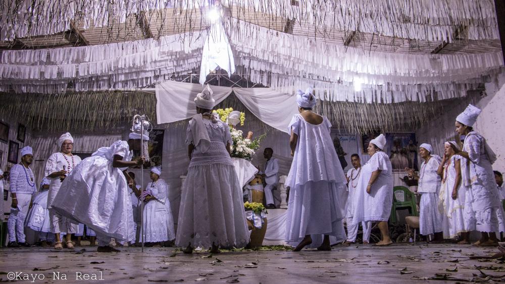 Imagem colorida de um ritual em um terreiro de candomblé. Em um salão espaçoso, vários homens e mulheres vestindo roupas brancas se reúnem e interagem em forma de círculo. No teto, várias fitas de cor branca e, no chão, várias folhas secas espalhadas.