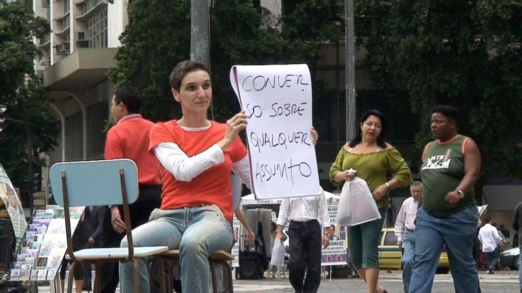 Mulher branca com cabelos curtos está em uma cadeira e diante de outra no meio de uma praça. Ela segura um cartaz em que está escrito 'Converso sobre qualquer assunto'.