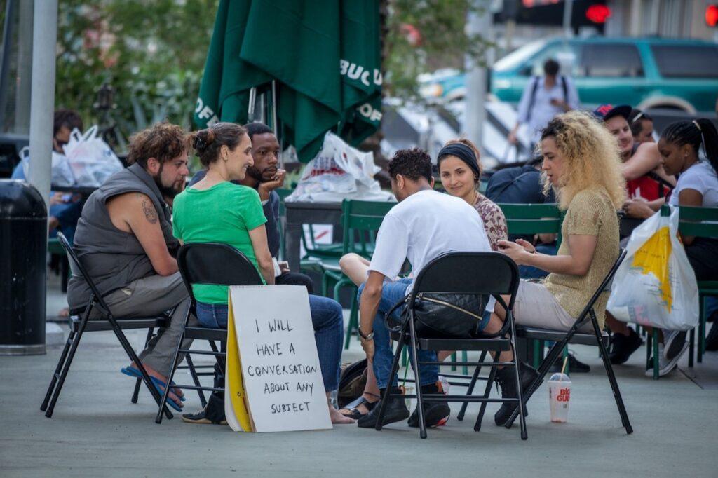 Imagem colorida de pessoas sentadas em uma roda de cadeira no meio de uma praça. Ao lado de uma das pessoas, um cartaz em que está escrito 'I will have a conversation about any subject'