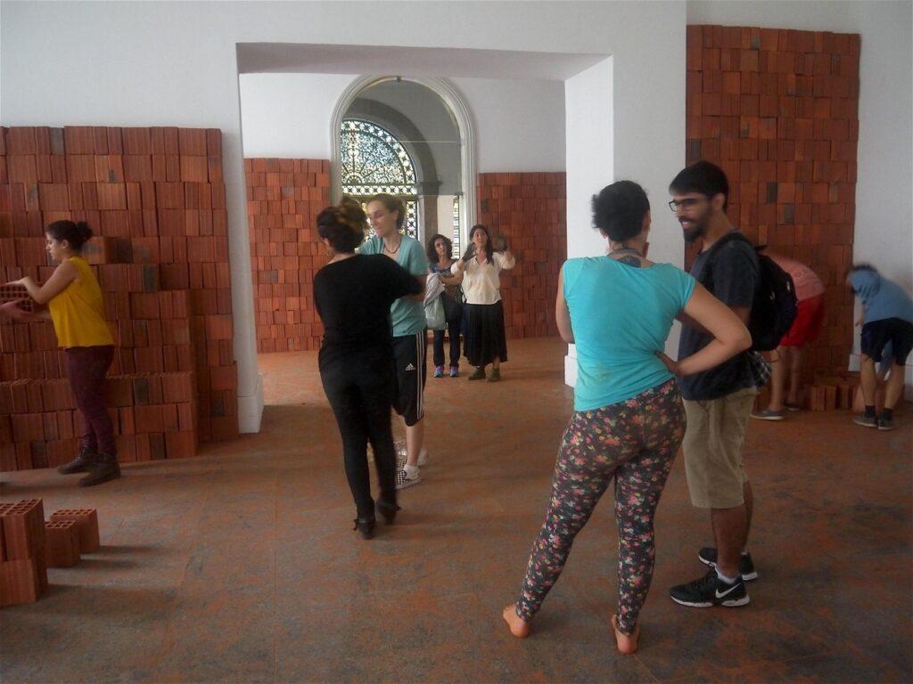 Imagem colorida de pessoas reunidas em uma sala com paredes brancas em que estão posicionados vários tijolos vermelhos. Eles formam uma espécie de segunda parede diante das paredes brancas.
