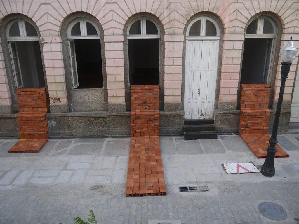 Imagem colorida de uma fachada na cor salmão. De algumas das janelas, saem um conjunto de tijolos vermelhos que são posicionados como se formassem uma espécie de estrada