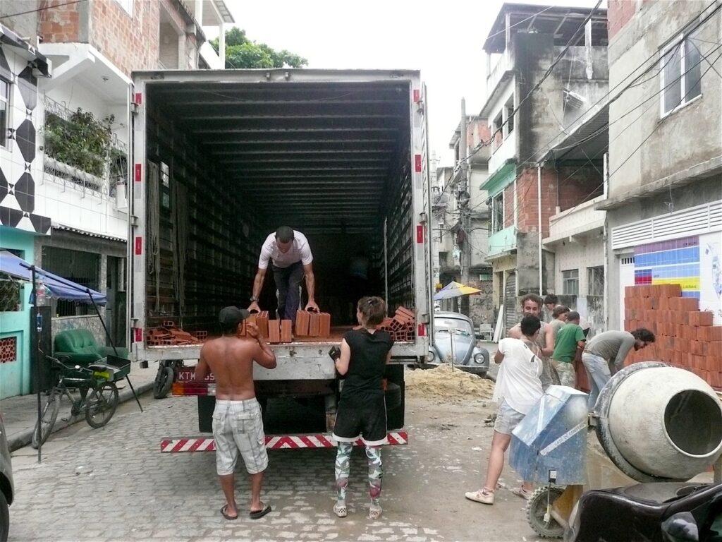 Imagem colorida de pessoas descarregando um caminhão no meio da rua. De dentro dele, as pessoas tiram vários tijolos.
