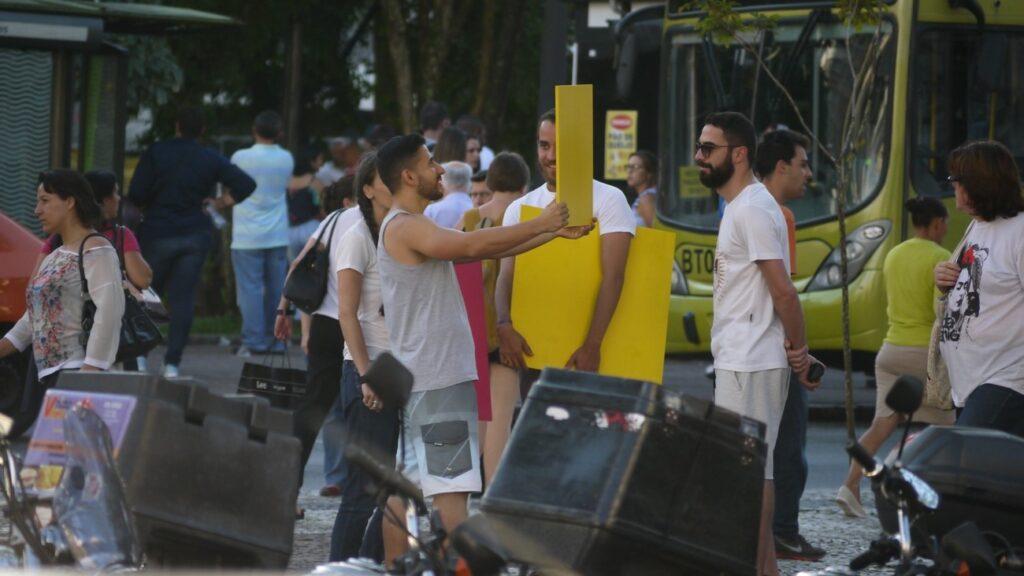 Imagem colorida de pessoas no meio da rua. Um homem levanta um cartaz amarelo diante do próprio rosto, enquanto é observado por outras pessoas.