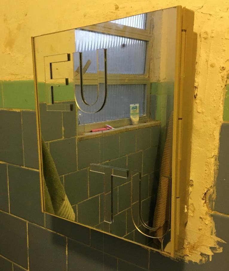 Imagem colorida de um espelho em um banheiro. Nesse espelho, pode-se ler as palavras EU e TU em relevo.