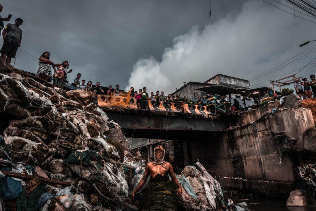 Imagem colorida de Uýra Sodoma, usando um vestido da cintura para baixo. Ela está em um espaço aberto, pouco abaixo de uma ponte. Ao lado esquerdo dela, um monte de lixo. ao fundo, uma ponte em que se pode ver um público que assiste à performance.