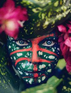 Imagem colorida de Uýra Sodoma com maquiagem verde com pontos brancos e traços vermelhos. Ela está no meio de folhas e flores