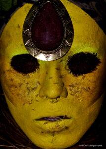 Rosto maquiado com cores amarelas. Na cabeça, uma joia dourada em forma de gota cobre toda a testa. Os olhos estão pintados completamente de preto